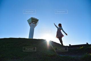 草の丘の上に立ちながら空中を飛んでいる男の写真・画像素材[2792161]