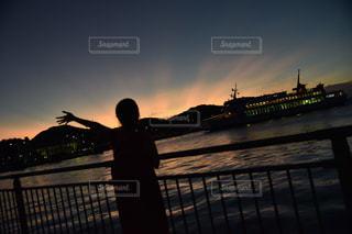 夕焼けの前に立っている人の写真・画像素材[2818286]