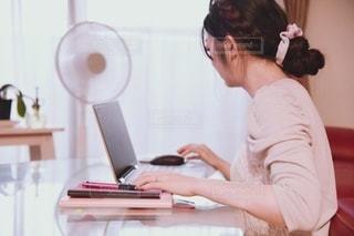 ラップトップを使ってテーブルに座っている人の写真・画像素材[3305437]