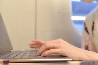 ラップトップコンピュータを使ってテーブルに座っている人の写真・画像素材[3358417]