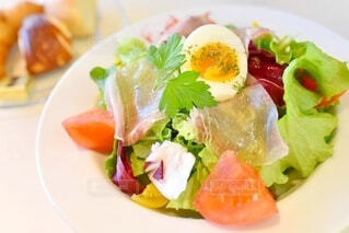 食べ物の皿をテーブルの上に置くの写真・画像素材[3948176]