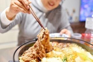 食べ物の皿を持ったテーブルに座っている人の写真・画像素材[3948575]