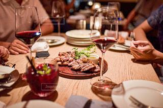 食べ物の皿を持ってテーブルに座っている人々のグループの写真・画像素材[3974987]
