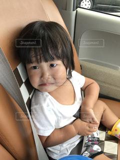 車の座席に座っている小さな女の子 - No.705364