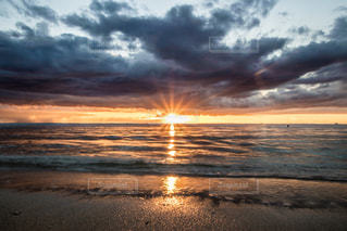 海の横にあるビーチに沈む夕日の写真・画像素材[914634]