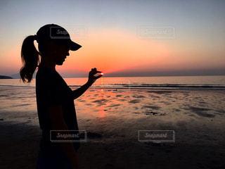 バック グラウンドで夕焼けのビーチに立っている人の写真・画像素材[961133]