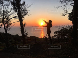 日没の前に立っている男の写真・画像素材[961134]
