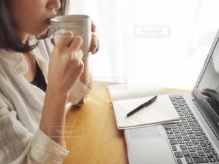 ノート パソコンの前でコーヒーを飲む女性の写真・画像素材[935055]
