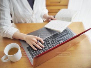 ラップトップ コンピューターを使用してテーブルに座っている人の写真・画像素材[935073]