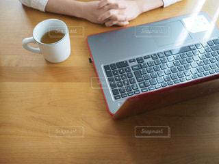 ラップトップ コンピューターを使用してテーブルに座っている人の写真・画像素材[935089]