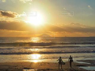 背景の朝陽とビーチの上を歩く人々 のグループの写真・画像素材[939398]