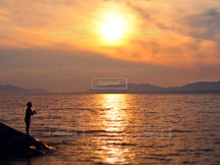 夕焼けと釣り人の写真・画像素材[955381]