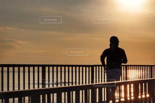 フェンスの横に立っている人の写真・画像素材[977766]