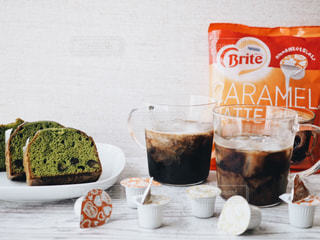 近くのコーヒー カップの横にあるテーブルの上に食べ物のアップの写真・画像素材[1252709]