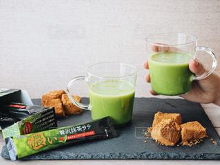 近くのコーヒー カップの横にあるテーブルの上に食べ物のアップの写真・画像素材[1293953]