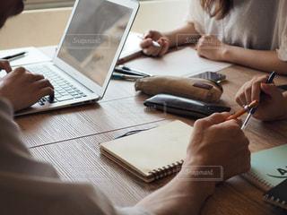 ラップトップ コンピューターを使用してテーブルに座っている人々 のグループの写真・画像素材[1319189]