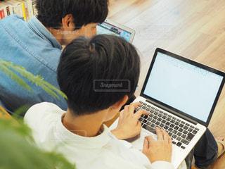 座ってパソコンで作業をしている男性の写真・画像素材[1574884]