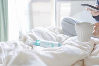 ベッドの上に座ってコーヒーを1杯の写真・画像素材[2094809]