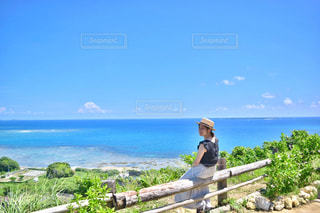 海を望むベンチに座っている男の写真・画像素材[897017]