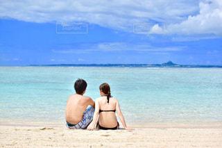 砂浜で座っている男の写真・画像素材[897059]