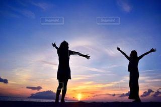 日没の前に立っている人々 のグループの写真・画像素材[929123]