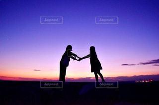 バック グラウンドで夕日を持つ男の写真・画像素材[957015]