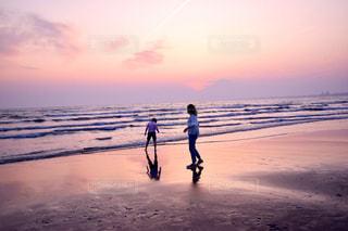 背景の夕日とビーチの上を歩く人の写真・画像素材[1287765]