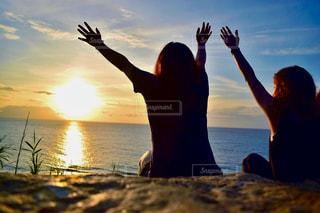 水の体の上に日没の前に立っている人の写真・画像素材[1287788]