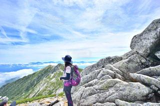 岩が多い丘の上に立っている人の写真・画像素材[1440963]