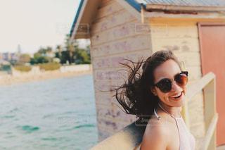 海辺で風に吹かれるサングラスをかけた女の子の写真・画像素材[1405930]