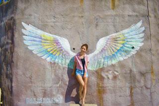 建物の前に立っている間凧を持っている人の写真・画像素材[712113]