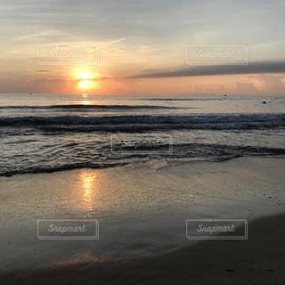 水の体の横にビーチに沈む夕日の写真・画像素材[1289690]