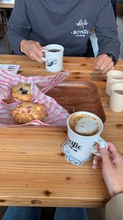 食べ物とコーヒーを飲みながらテーブルに座っている男の写真・画像素材[2293883]