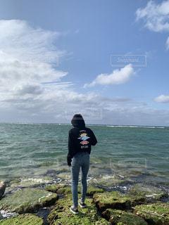 海の隣の水域の隣に立っている男の写真・画像素材[2293911]
