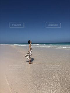 海の隣のビーチを横切って歩いている男の写真・画像素材[2431074]