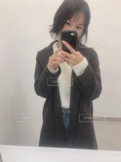 カメラに向かってポーズをとる鏡の前に立つ女性の写真・画像素材[2453343]