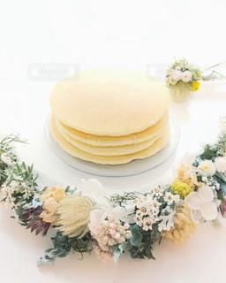 テーブルの上の花の花瓶をのせた白プレートの写真・画像素材[958401]
