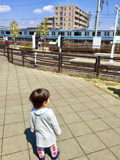 フェンスの横に立っている小さな男の子 - No.757903