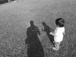 草の中に立っている小さな男の子の写真・画像素材[818524]