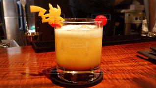 テーブルの上のコーヒー カップの横にあるオレンジ ジュースのガラスの写真・画像素材[1413134]