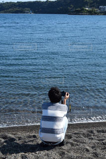 水の体の近くの浜辺に座っている人の写真・画像素材[2141826]