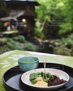 テーブルの上の皿の上に食べ物のボウルの写真・画像素材[1051243]