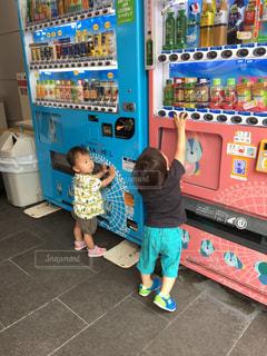 店の前に立っている少年の写真・画像素材[1184903]