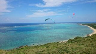 水の体の近くのビーチに凧の飛行の人々 のグループの写真・画像素材[920673]