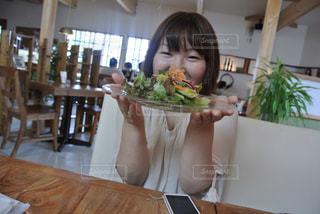 食事のテーブルに座っている女性の写真・画像素材[750447]