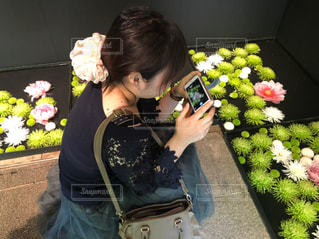 花の前に立つ女性の写真・画像素材[2291959]