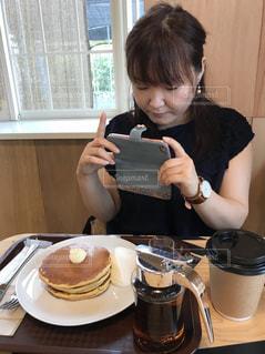 コーヒーを飲みながらテーブルに座っている人の写真・画像素材[2291962]
