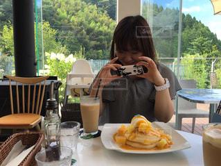 食べ物を食べるテーブルに座っている人の写真・画像素材[2291967]