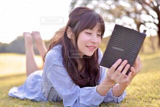 若い女の子が草の中に座っているの写真・画像素材[3694472]