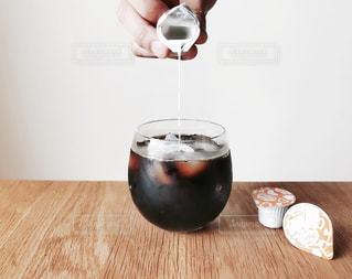 木製テーブルの上に座っているグラスワインの写真・画像素材[1245689]